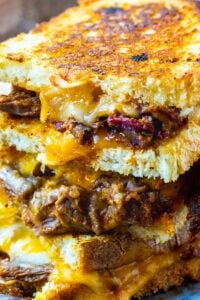 Brisket Grilled Cheese halves stacked on top od each other.