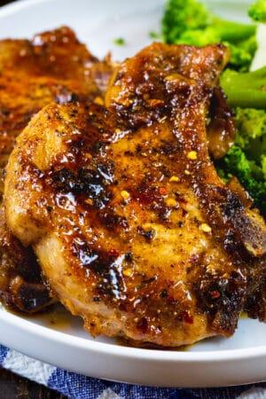 Two Brown Sugar Garlic POrk Chops on a plate with broccoli.