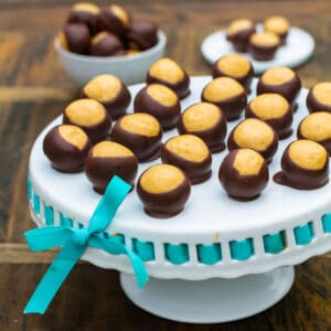Buckeye Balls on a white cake stand.