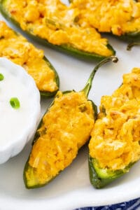 Buffalo Chicken Jalapeno Poppers on plate with bowl of blue cheese dip.
