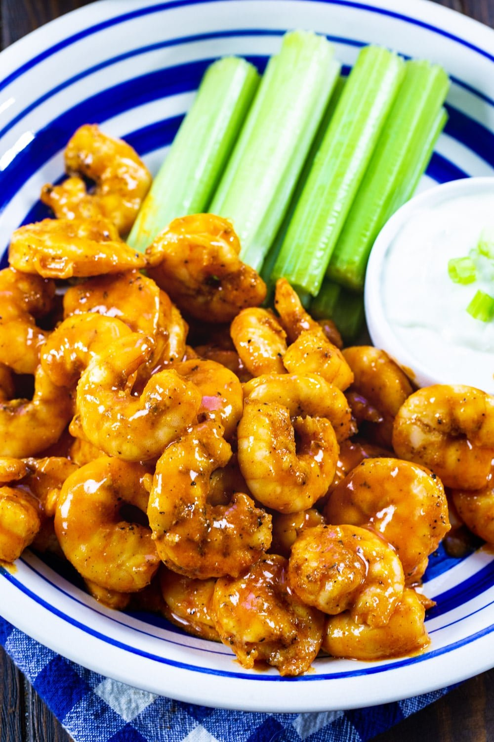 Shrimp coated in buffalo sauce on a blue and white plate.