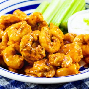 Buffalo Shrimp on a plate with celery and small bowl of dressing.