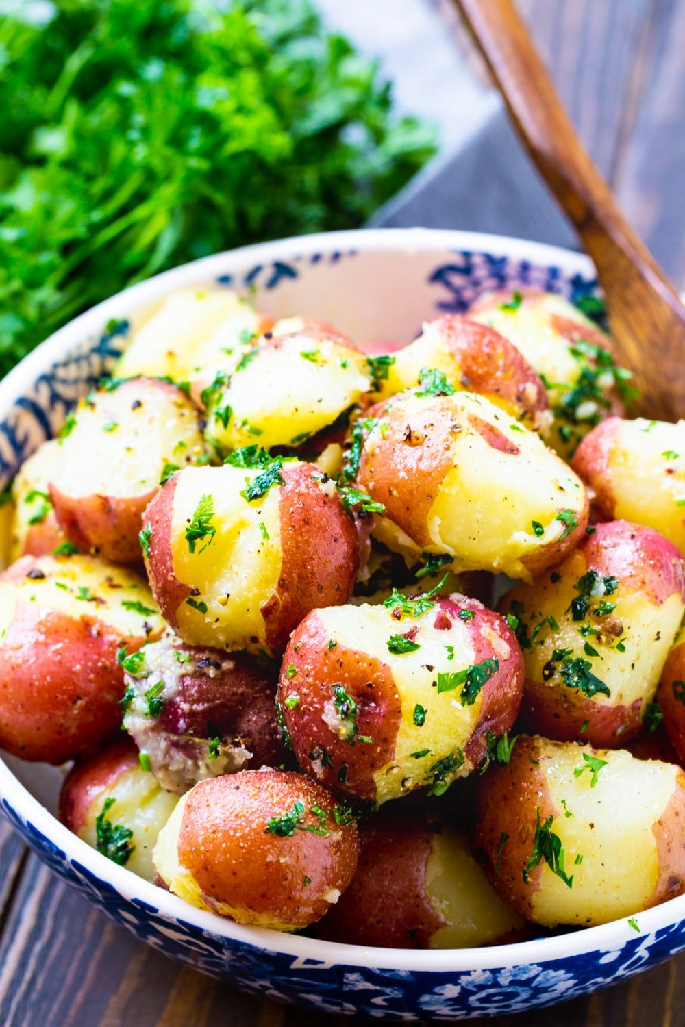 Butter Parsley Potatoes in a bowl with a fresh bunch of parsley.