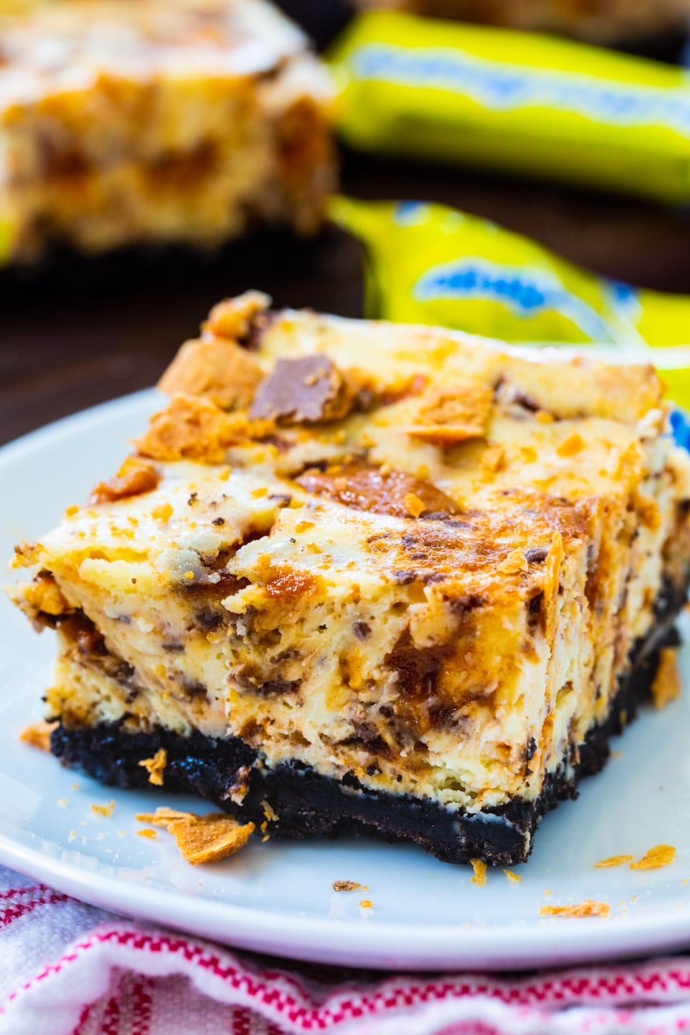 Butterfinger Cheesecake Bar on a small plate surrounded by mini butterfinger candies.