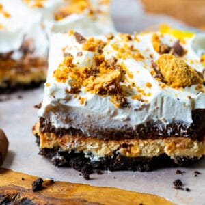 Slice of Butterfinger Chocolate and Peanut Butter Lush on a piece of parchment paper.