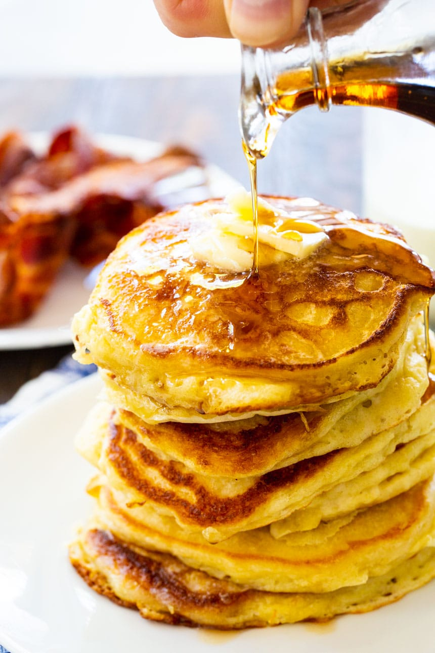 Stack of Buttermilk Pancakes with bacon in the background.