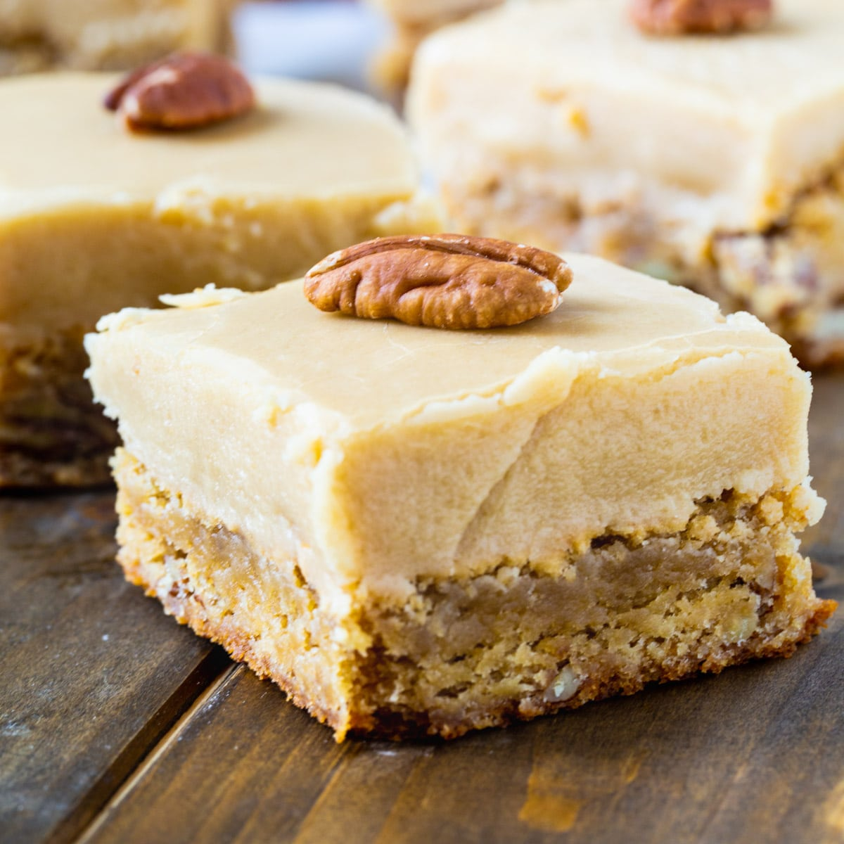 Butterscotch Blondies cut into squares with whole pecans on top.