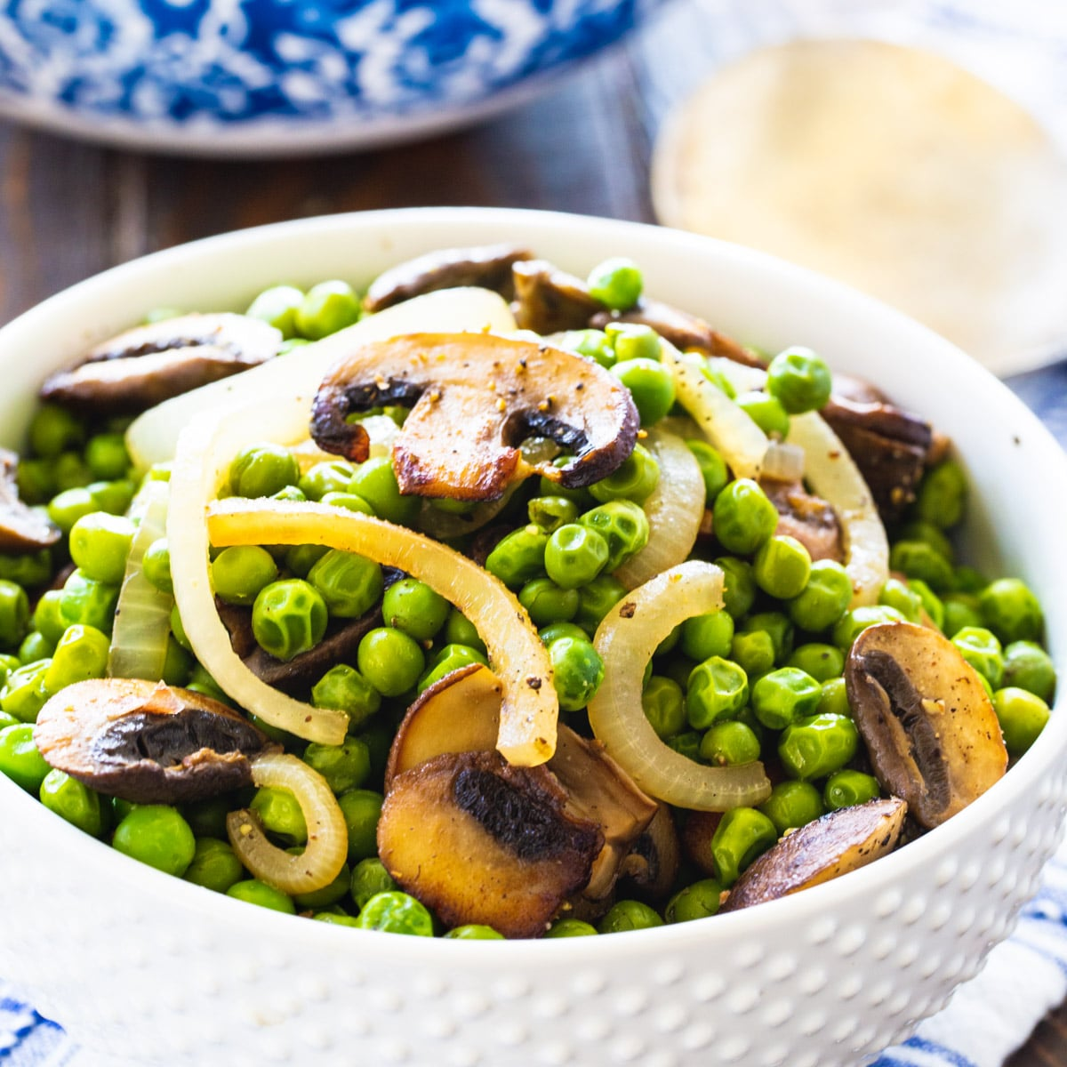 Buttery Peas and Mushrooms in a white bowl.