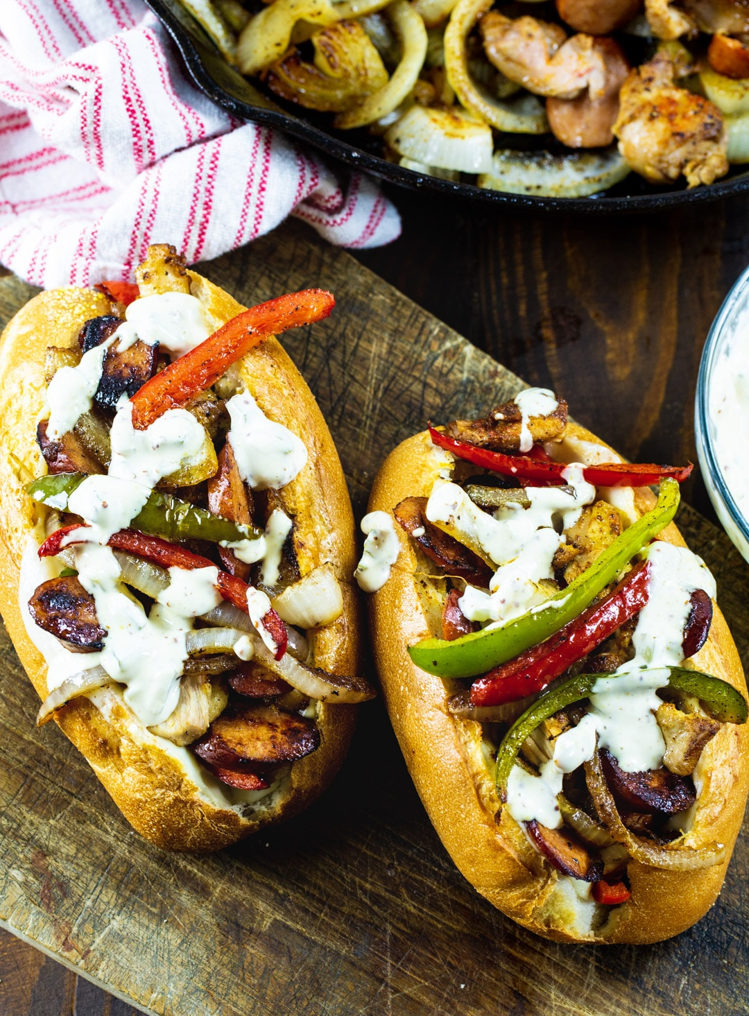 Two Chicken and Andouille Subs with skillet full of filling.