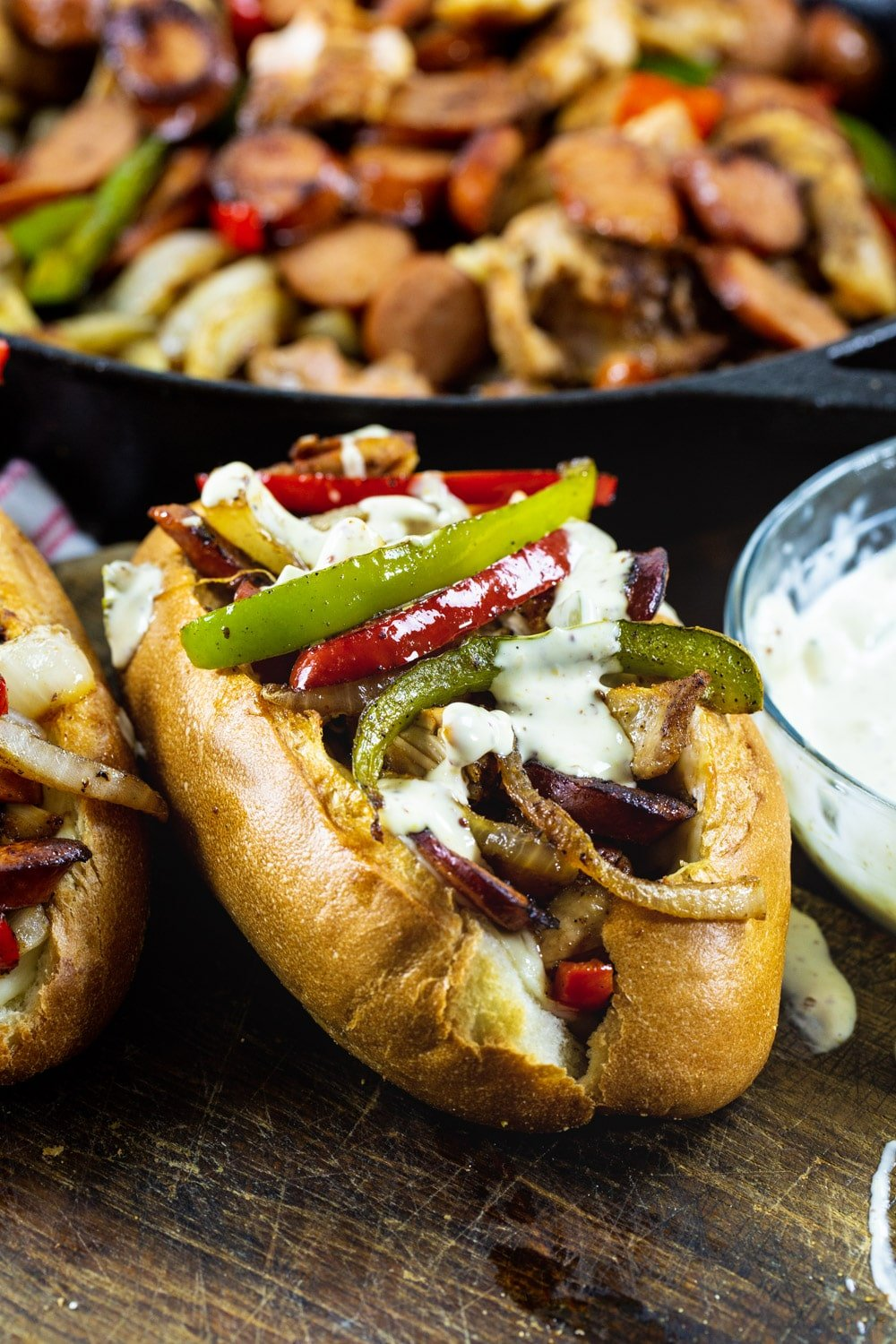 Cajun Chicken and Andouille Subs with skillet full of chicken and sausage filling in background.