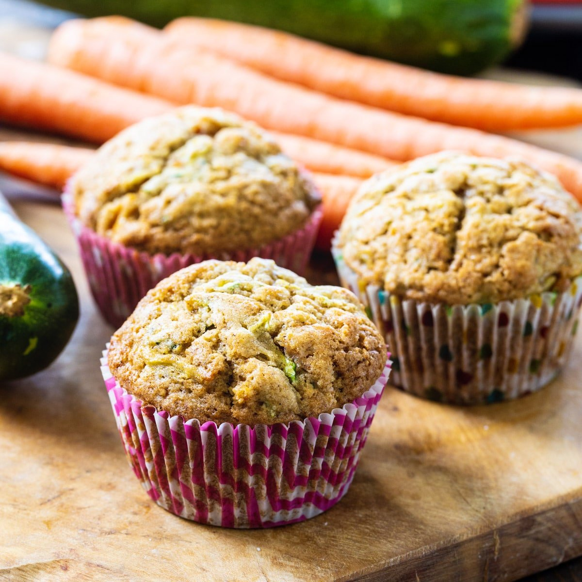 Three Carrot Zucchini Muffins on a wooden board.