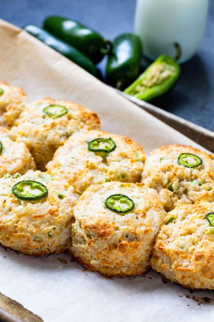 Biscuits on baking sheet with jalapenos in background.