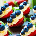 Red, White, and Blue Cheesecake Strawberries on a dark wood board.