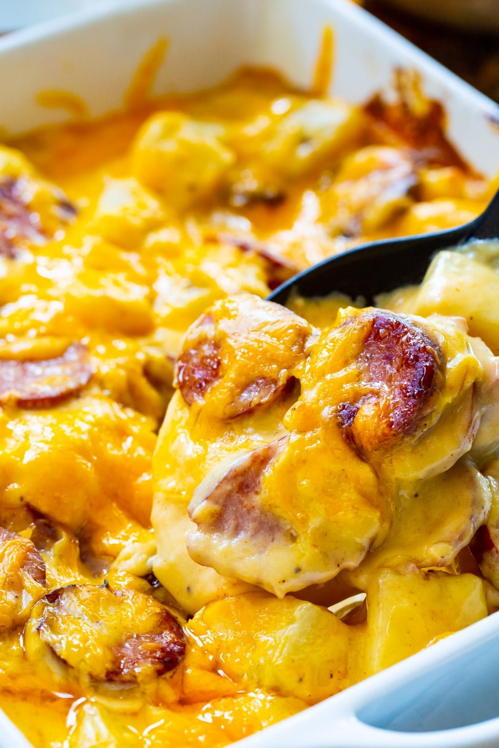 Spoon scooping up Cheesy Potatoes with Smoked Sausage
