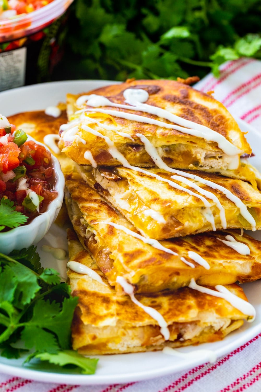 Chicken, Bacon and Ranch Quesadillas drizzle with ranch on a plate.