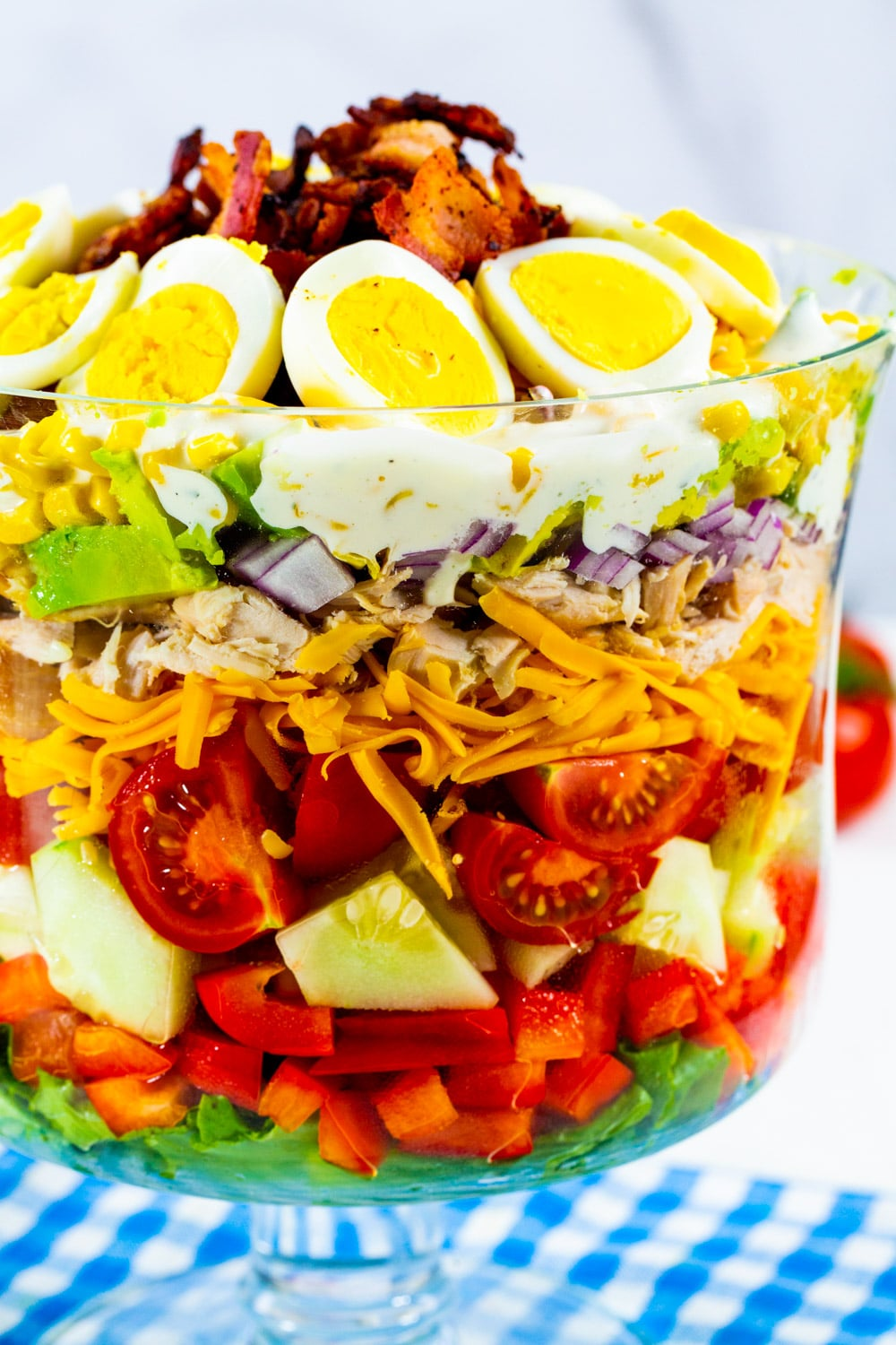 Layer Salad topped with hard-boiled egg and bacon in a trifle dish.