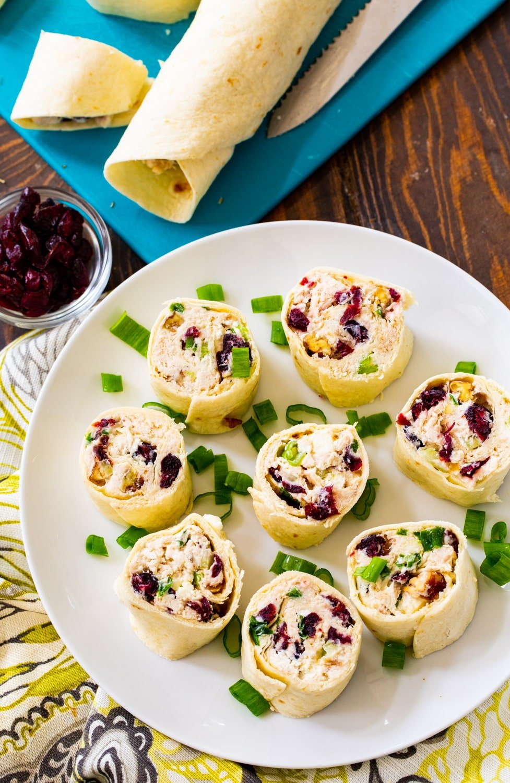 Cut pinwheels on a plate with uncut tortilla rolls on a cutting board.