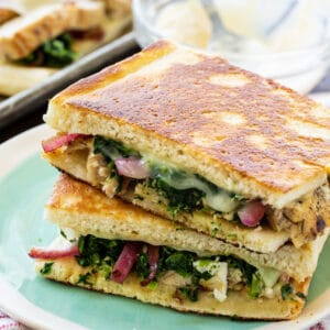 Two Pieces of panini stacked on a plate.