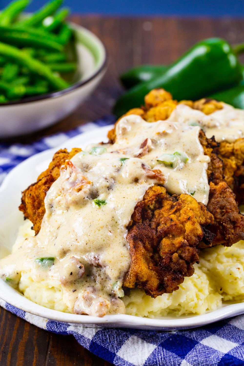 Chicken Fried Steak on a serving platter with bowl of green beans in background.
