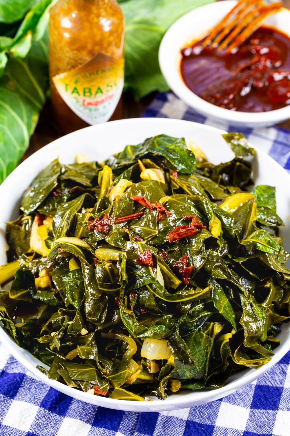 Chipotle Collard Greens in bowl with a bottle of hot sauce.