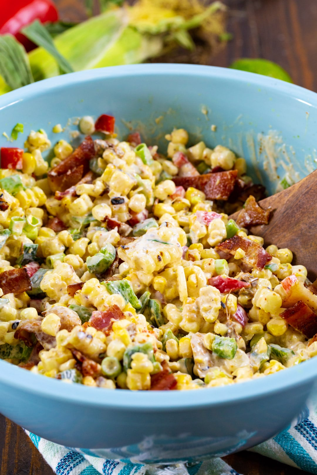 Corn Salad in blue mixing bowl with wooden spoon.