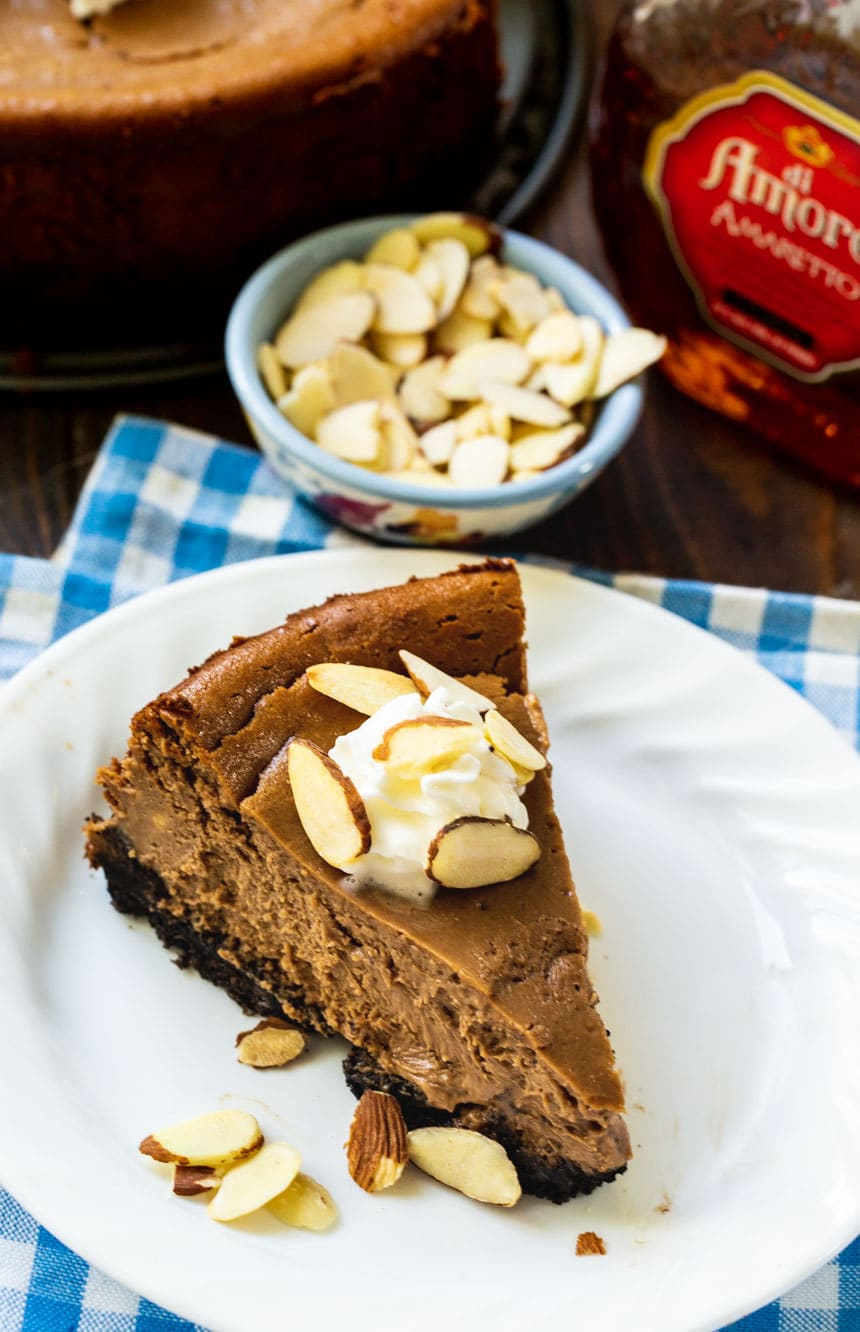 Slice of Chocolate Amaretto Cheesecake on plate with bowl of almonds.