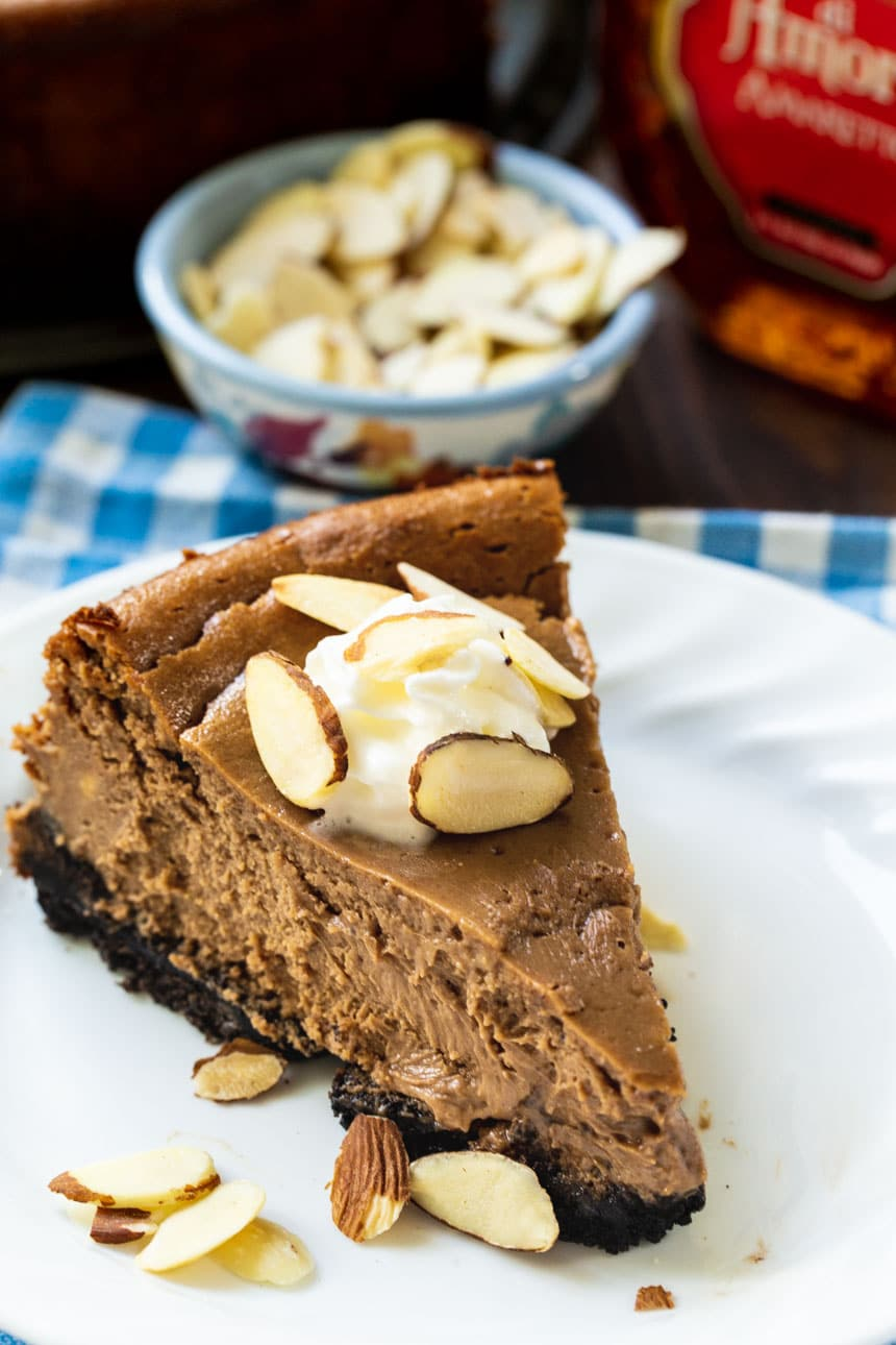 Chocolate Amaretto Cheesecake topped with whipped cream and sliced almonds.