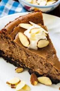 Slice of Chocolate Amaretto Cheesecake topped with whipped cream and sliced almonds.