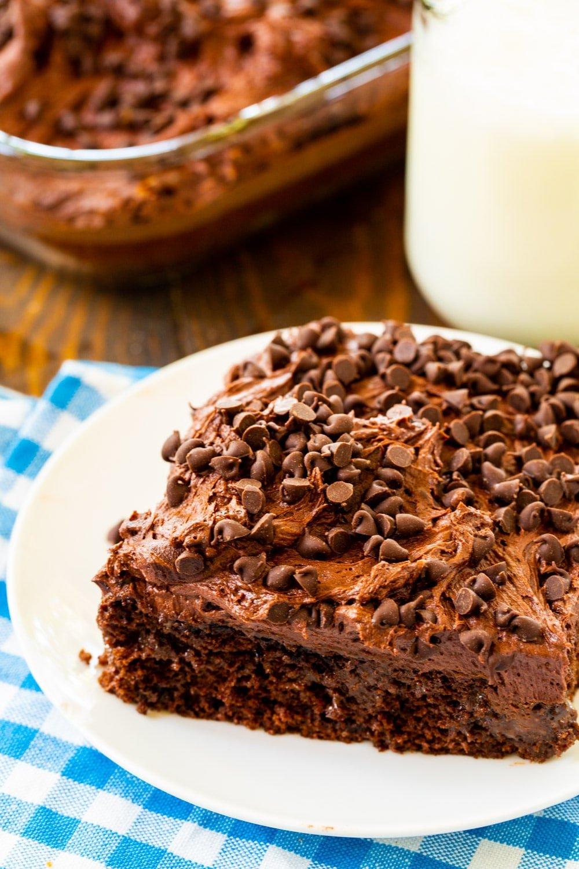 Chocolate Poke Cake on a plate with jug of milk.