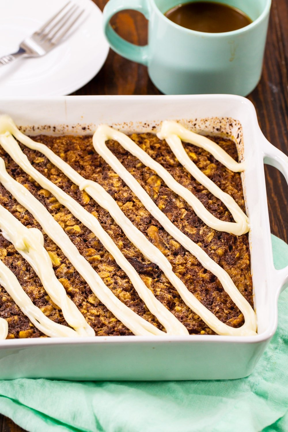 Baked Oatmeal topped with cream cheese glaze in a baking dish.