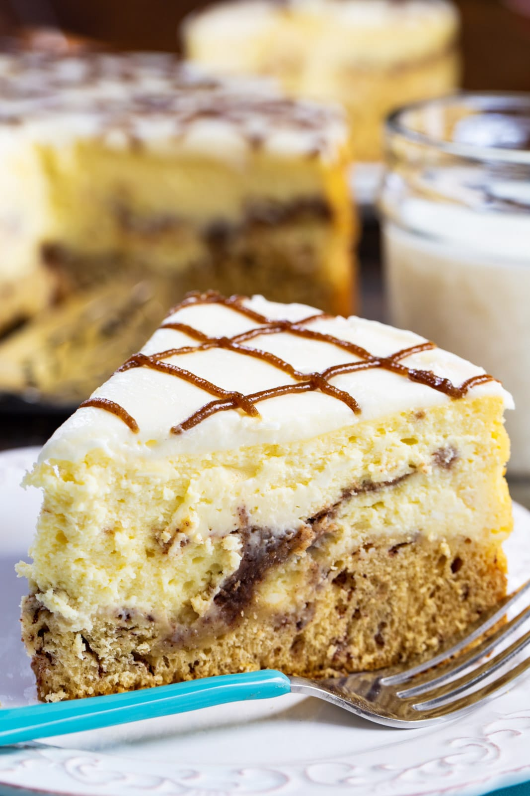 Slice of Cinnamon Roll Cheesecake on a plate with a fork.