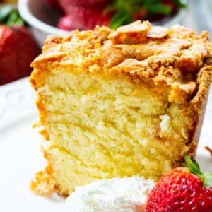 Slice Of Classic Southern Pound Cake with whipped cream and a strawberry.