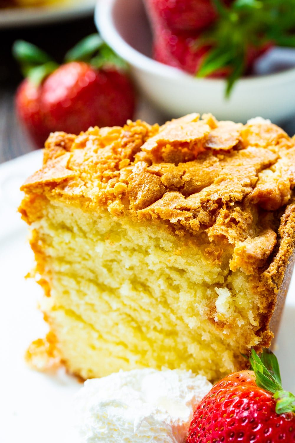 Slice of Classic Southern Pound Cake with fresh strawberries.