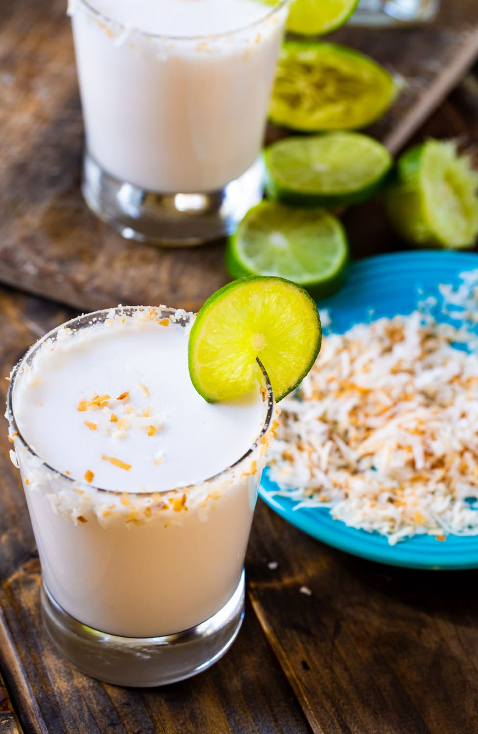 Margarita in aglass with plate of toasted coconut.