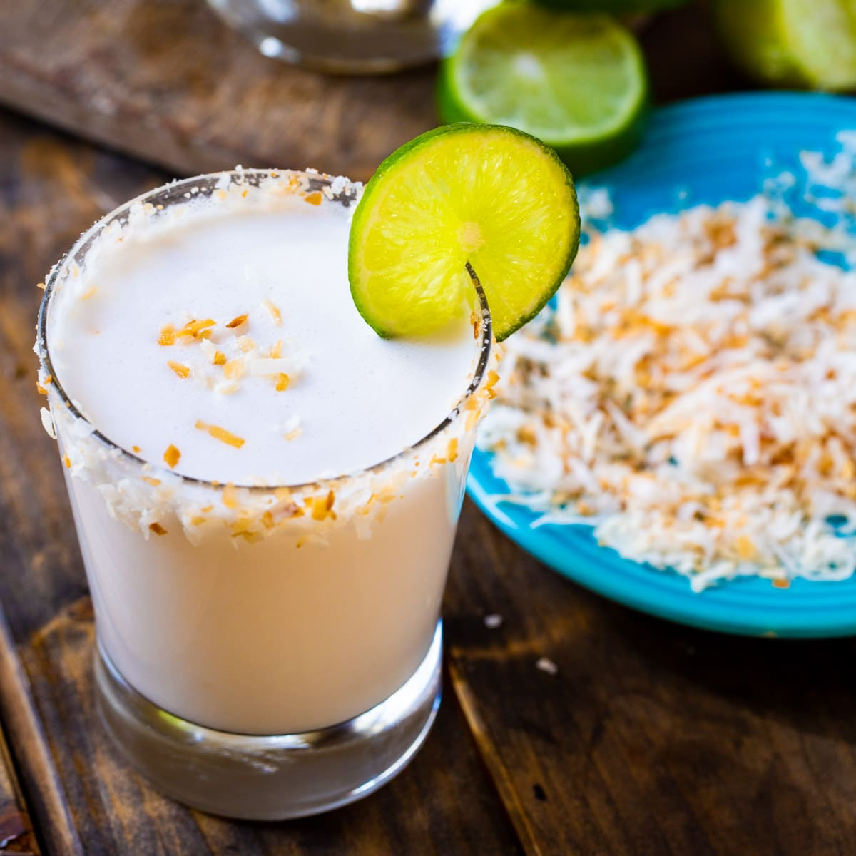 Coconut Margarita in a glass with toasted coconut around rim.