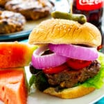 Cola Burgers topped with tomatoes, and red onions.