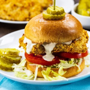 Cornflake Crusted Chicken Sandwich on a plate with dill pickle slices.