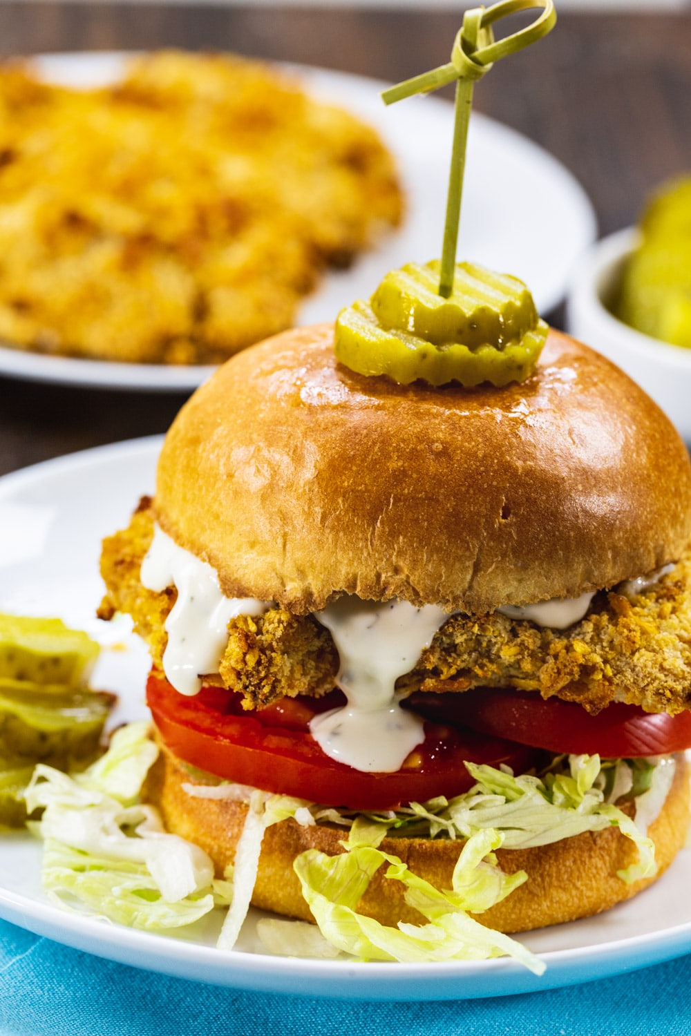 Close-up of Cornflake Crusted Chicken Sandwich with ranch dressing drippinf down.