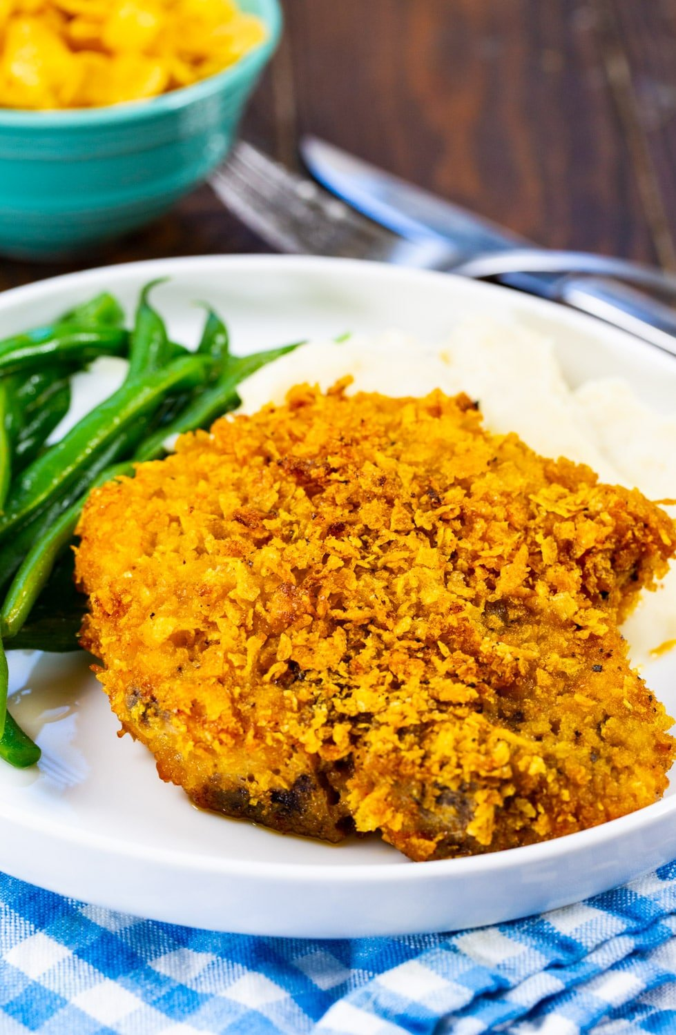 Cornflake Crusted Baked Pork Chop on plate with mashed potatoes and green beans.