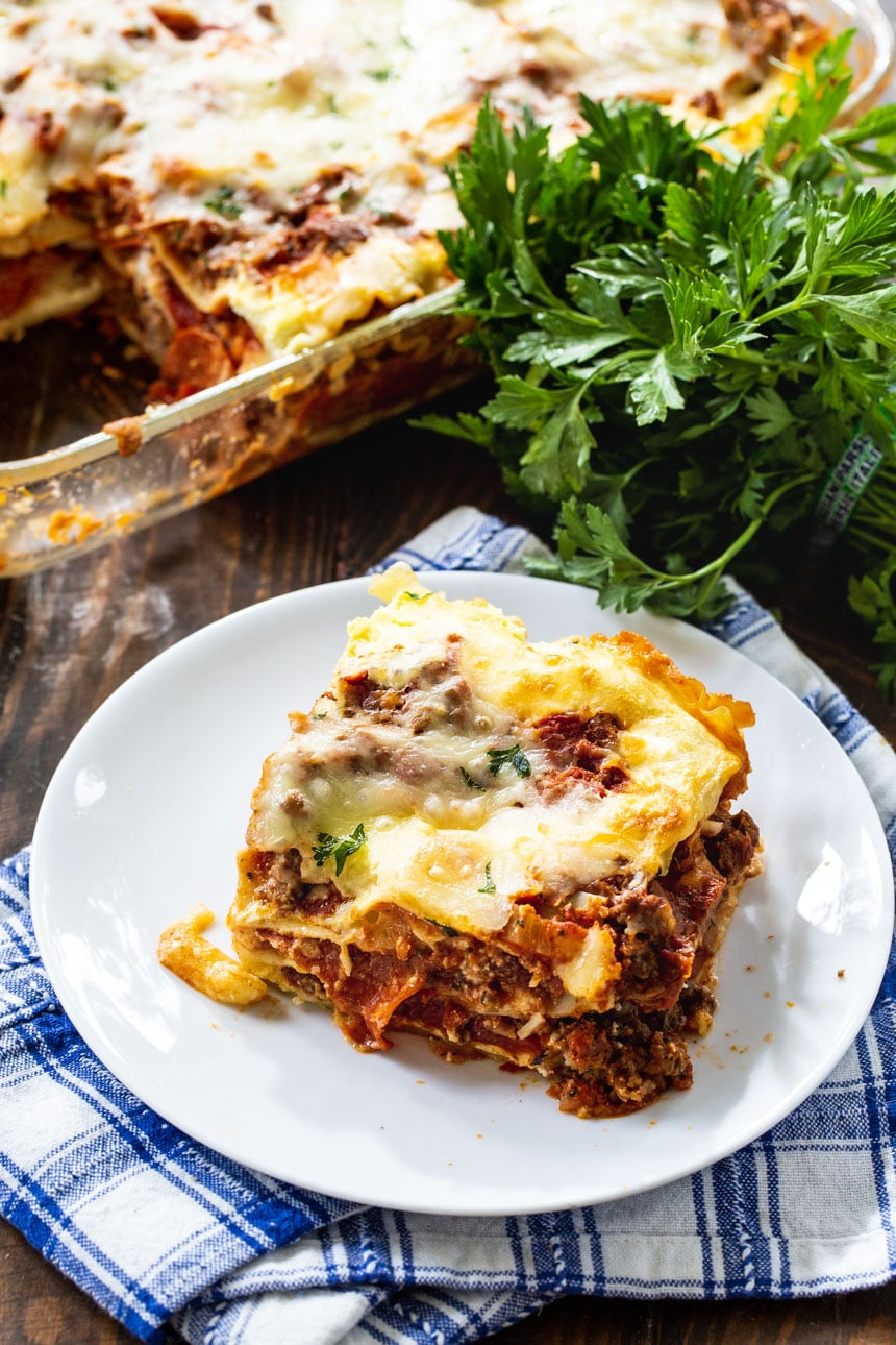 Slice of lasagna with parlsey behind it.