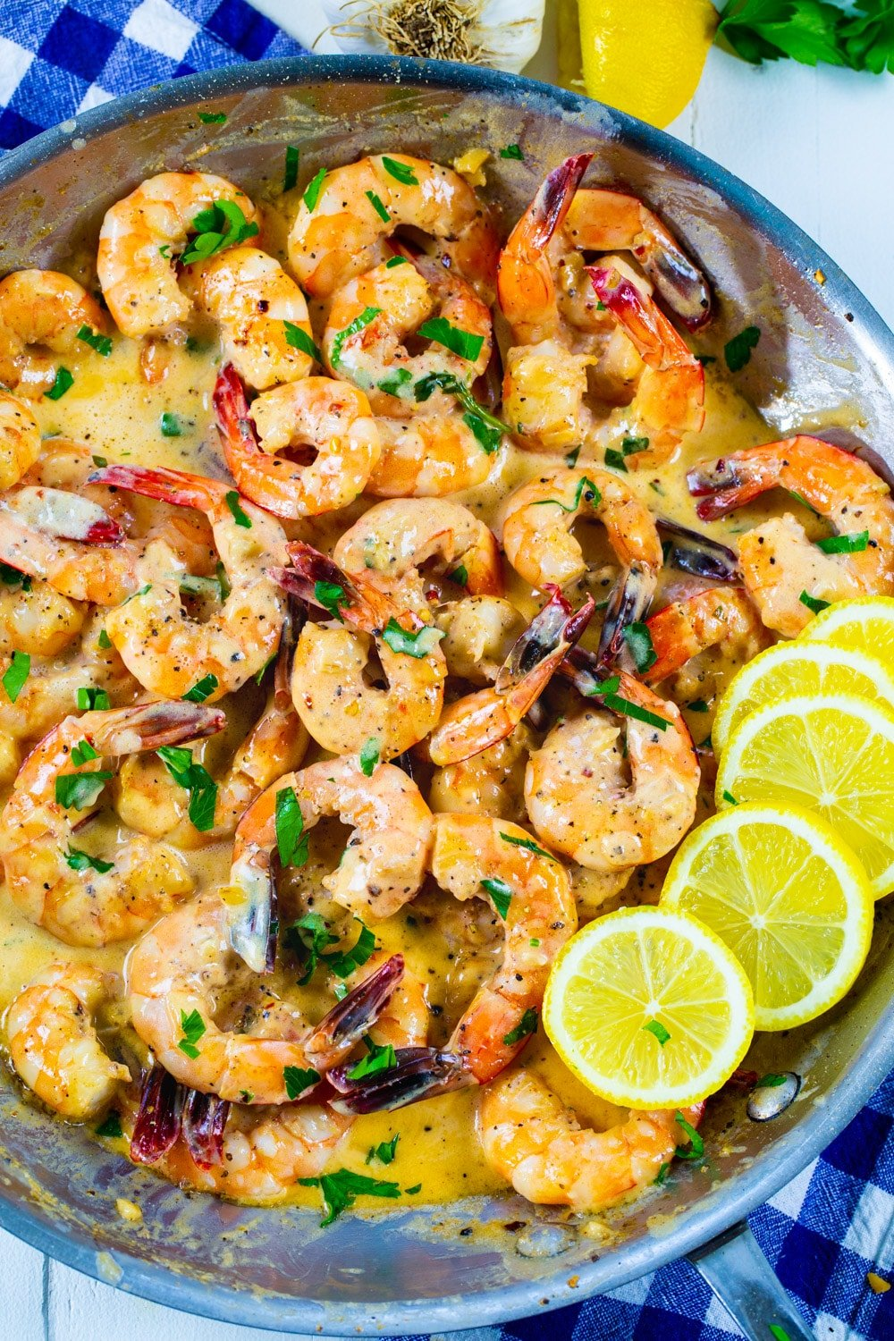 Cooked shrimp in a skillet with lemon slices.