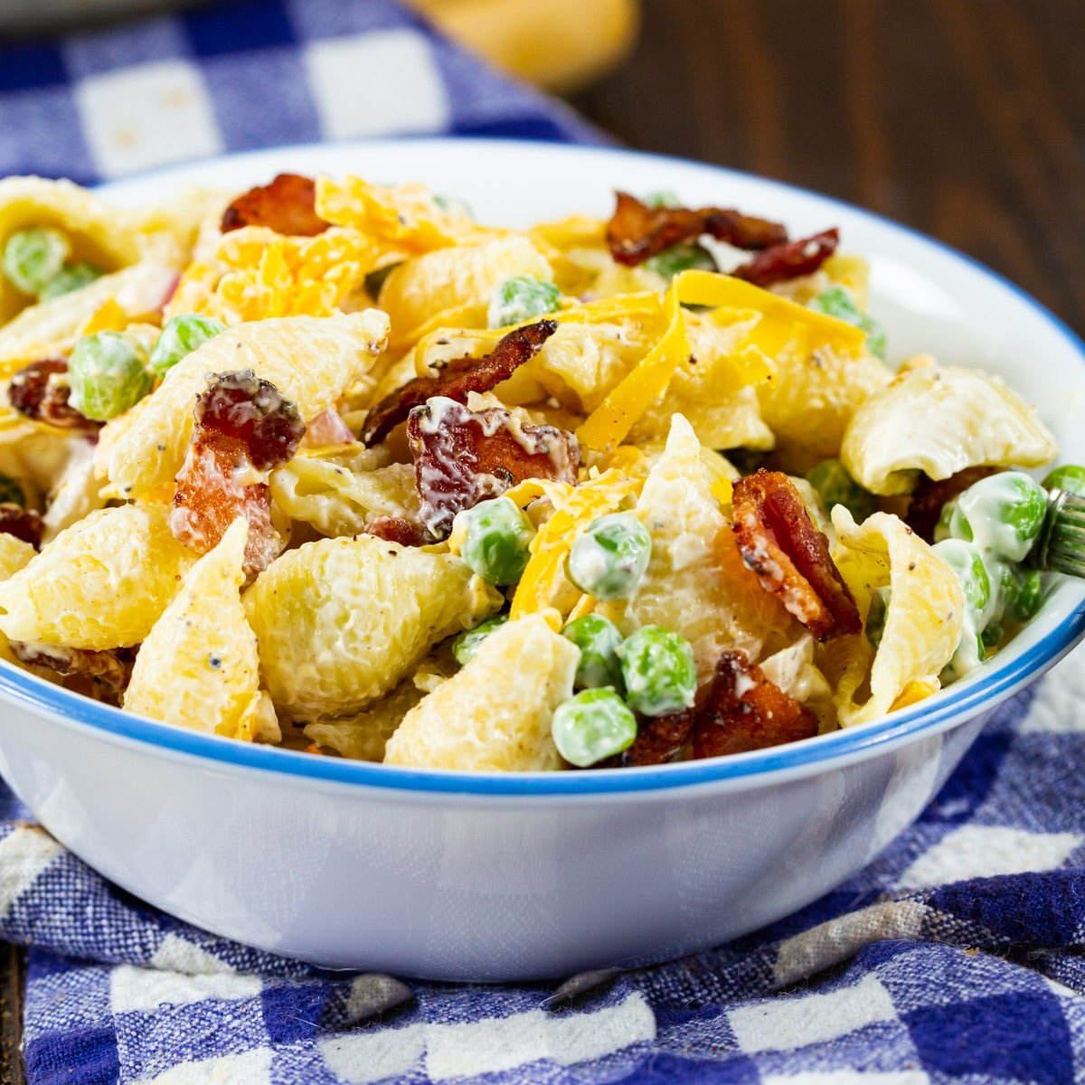 Small bowl full of Creamy Pasta Salad with Peas and Bacon.