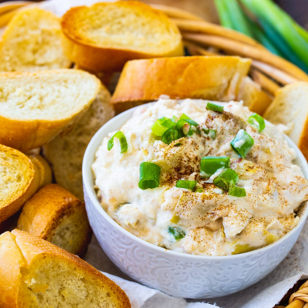 Crock Pot Crab Artichoke Dip in bowl surrounded by toasted baguette slices.