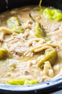 Crock Pot Mississippi Chicken and Noodles in black slow cooker.
