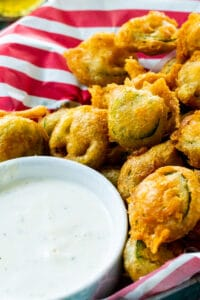 Deep Fried Jalapeno Slices in a basket with small bowl of Ranch dressing.