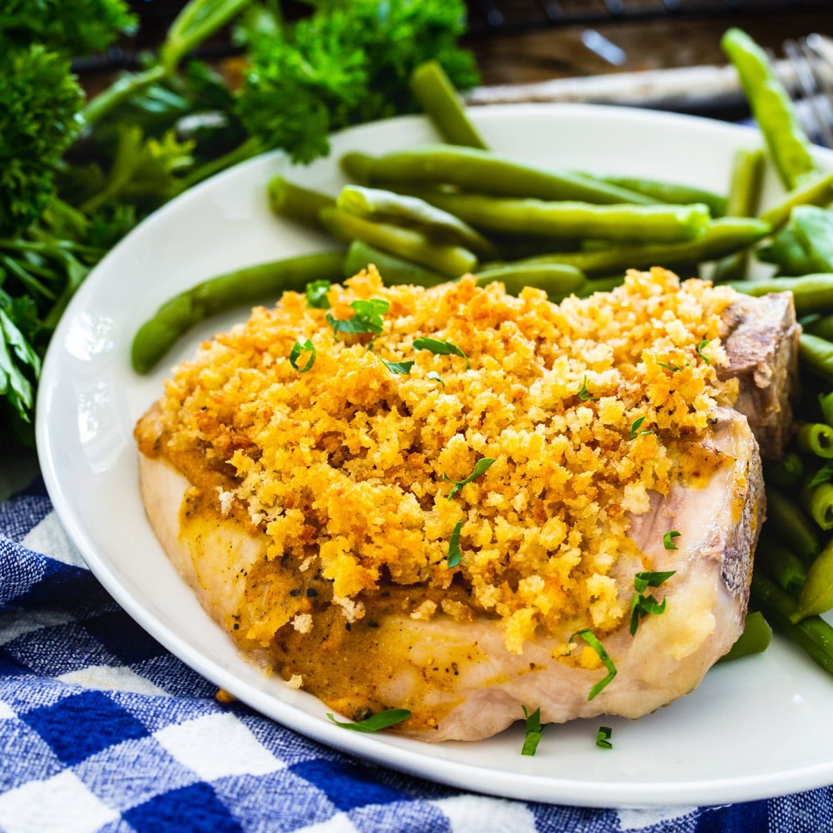 Deviled Pork Chops on a plate with green beans.
