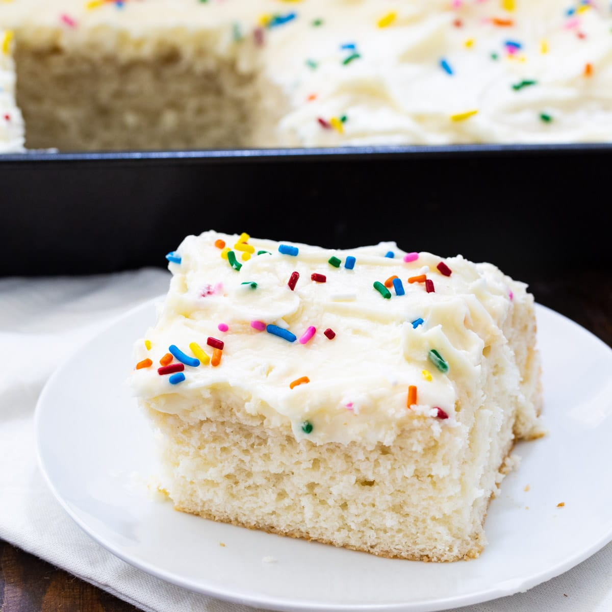 Slice of Doctored Cake Mix White Sheet Cake on a plate.
