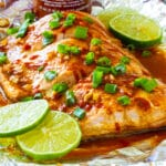 Firecracker Baked Salmon with lime slices on a baking sheet.