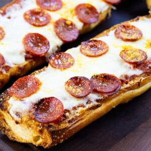 Two Pieces of Pepperoni French Bread Pizza on a cutting board.