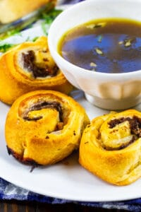French Dip Pinwheels on a plate with a bowl of Au Jus.
